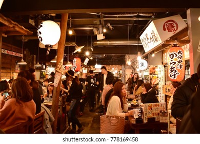 OSAKA, JAPAN - DECEMBER 31, 2016 : People are using their new year holiday in street food arcade and enjoying Japanese traditional street food and drinks