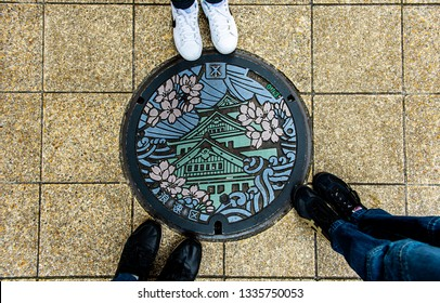 OSAKA, JAPAN - DECEMBER 31, 2018 : Feet of tourist standing on the manhole Osaka castle in the cover, it's art work at sidewalk on the street, mentioned that they had visited at Osaka, Japan.