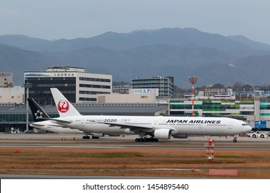 Osaka, Japan. December 7, 2018. Japan Airlines Boeing 777-346 Reg. JA751J Taxi to Runway for Departure from Osaka Itami International Airport with ATC Tower Background
