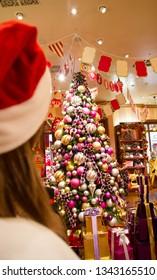Osaka, Japan - December 8, 2013: a girl in Santa hat looking at beautifully decorated Christmas tree in the shop at USJ Universal Studios Japan theme park
