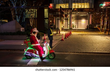 Osaka, Japan - December 8, 2018: Man dressed as Santa Claus on brightly lit motorbike looking at phone