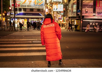 Osaka, Japan - December 8, 2018: Big Echo street staff shifts to keep warm on cold night as she waits for potential customers