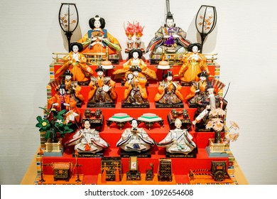 "OSAKA, JAPAN, February 19, 2018 : Ancient antique ""Hina Matsuri"" dolls in kimonos show on shelf and red velvet. Hina Matsuri is symbolic of Japanese Girl's Festival in 3 March of every year."
