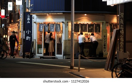 Osaka, Japan - February 2, 2018: Two businessmen drink outside busy Japanese standing bar