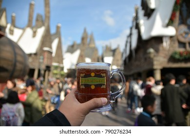 Osaka, Japan - JAN 6, 2017 : Hand holding glass of Butter beer in Wizarding World at Universal Studios Japan.
