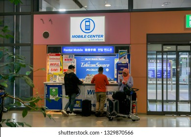 OSAKA, JAPAN, January 13, 2019 : Tourists are asking price and how to use rental wifi and mobile phone sim card for tourist at booths stand in Kansai International Airport.