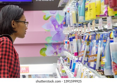 OSAKA, JAPAN, JUL 01 2017, A young woman chooses cosmetics at a store. Asian girl purchases drugstore at a supermarket. Buying cosmetics in a Japanese shop.