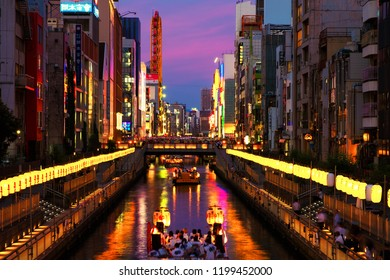 OSAKA, JAPAN - JULY 13, 2018: A sunset night view of the city channel with boats passing by and colorful illuminated buildings along the enbankment.