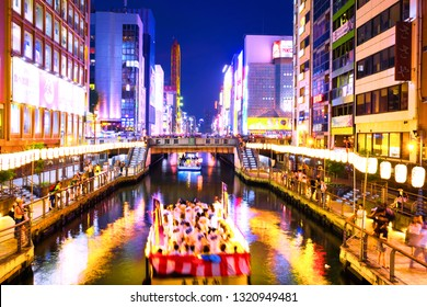 OSAKA, JAPAN - JULY 13, 2018: A sunset night view of the city channel with boats passing by in Osaka, Japan and colorful illuminated buildings along the enbankment.