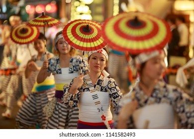 Osaka, Japan - July 23, 2018: Young woman with red and yellow paper umbrellas participate in a parade at the Tenjin Festival, one of the largest summer festivals in Japan