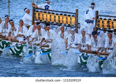 Osaka, Japan - July 23, 2018: Young men create large splashes with their oars as they turn their boat during the Tenjin Matsuri