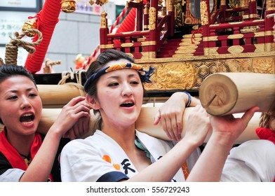 Osaka, Japan - July 25, 2012: Facial shot of unidentified young women worshipping the golden shrine in Tenjin Matsuri, Osaka's biggest festival