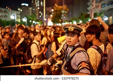 Osaka, Japan - July 25, 2015: Policeman working crowd control at the Tenjin Matsuri summer festival