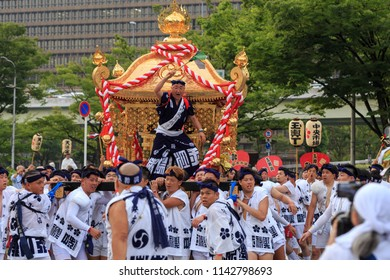 Osaka, Japan - July 25 2018: Young men strain to lift portable shrine as leader yells encouragement from above