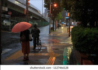 Osaka, Japan - July 5, 2018: Woman with umbrella and man riding bicycle wait to cross street during heavy rain