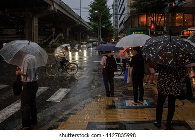 Osaka, Japan - July 5, 2018: Pedestrians wait to cross flooded street in heavy rainstorm