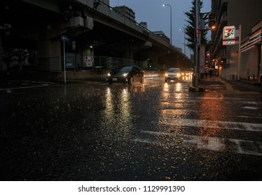Osaka, Japan - July 5, 2018: Car headlights reflect off flooded street during heavy rain storm which caused damage and flooding throughout southern Japan