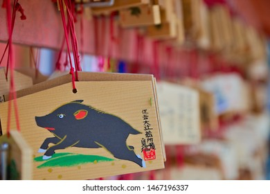 "Osaka, Japan - June 13, 2019: Shintoist Ema depicting a wild boar and there is written ""Happy 2019 year of the wild board"" in Japanese. Selective focus."