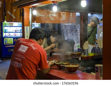 Osaka, Japan - June 20, 2010: Customers of a ramen street bar in Dohtombori entertainment district on June 20, 2010. Ramen shops are extremely popular in Japan.