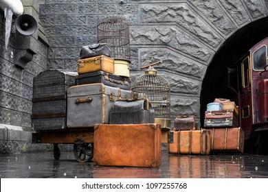 OSAKA, JAPAN - May 13, 2017 : Hogwarts Express train, Universal Studio, Osaka, Japan. Old vintage movie props, luggage, suitcase, bird cages at the train platform