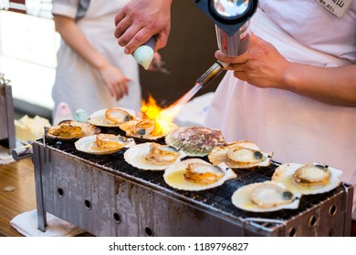 OSAKA, JAPAN - MAY 20, 2016: Street food vendor grilling the scallops in Dotonbori, Osaka, Japan.