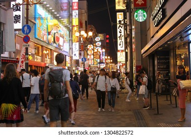 OSAKA, JAPAN - May 28, 2018. Crowds of men and women are shopping at night in busy Dotonbori street with neon billboards and Starbucks Coffee store. Namba district.