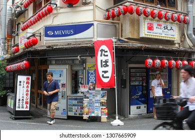 OSAKA, JAPAN - May 28, 2018. Man has bought cigarettes in tobacco shop and other man is smoking in outdoor neighborhood street with red Japanese lanterns, Minami Namba district.