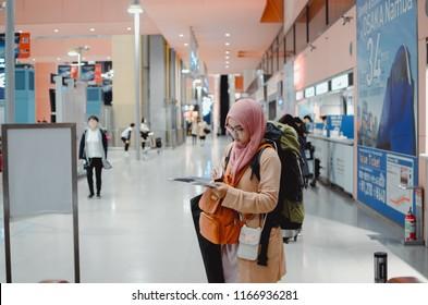 Osaka, Japan - November 2, 2017 - A muslim woman with a travel backpack reading a map as a tourist at Kansai International Airport