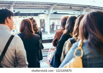 Osaka, Japan - November 2, 2017 - Japanese people queuing for boarding a train in Kyoto.Japanese people queuing for boarding a train in Kyoto.