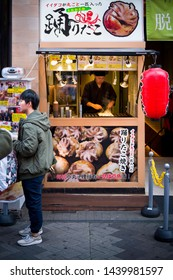 Osaka, Japan - November 2 2018: Chef cooking Takoyaki ball dumplings or Octopus balls. Takoyaki balls are made with octopus, wheat flour-based batter and pan. Takoyaki is a snack and street food speci