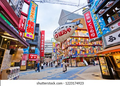 Osaka, Japan - November 2018: Tsutenkaku tower and Shinsakai entertainment district people can be seen waking past the brightly lit shops.