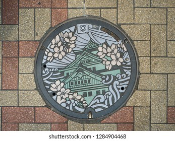 OSAKA, JAPAN - NOVEMBER 22, 2017 - 17.29: A Manhole cover in Japan normally was made as art. Normally represent the symbol of the places. Here is Osaka Castle with cherry blossom.