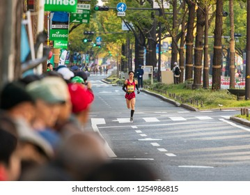 Osaka, Japan - November 25, 2018: Lone runner out ahead of main Osaka Marathon pack as fans look on
