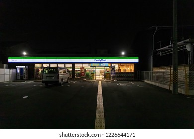 Osaka, Japan - November 6, 2018: Yellow line for visually impaired people leads through dark parking lot into FamilyMart convenience store