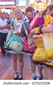 Osaka / Japan - October 1, 2017: Young girls dressed in flirtatious french maid costumes calling on passerby to visit maid cafe in Dotombori area of Osaka