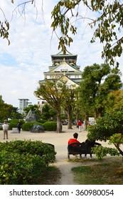 OSAKA, JAPAN - OCTOBER 15,2015: A man sitting and looking at Osaka Castle