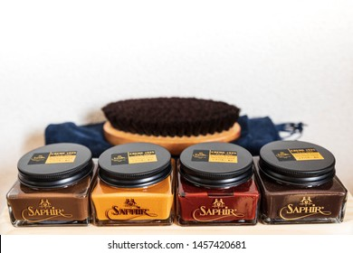 Osaka, Japan - Saphir shoe cream in differing colors from light brown to mahogany in front of circular horsehair polishing brush