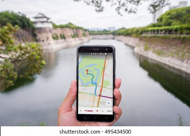 OSAKA, JAPAN - SEPTEMBER 15: Unidentified man hold a phone while using Google Maps in his hand near the river and Osaka Castle on September 15,2016 in Osaka, Japan