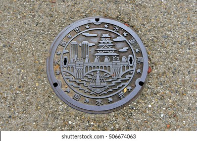 OSAKA, JAPAN - SEPTEMBER 25 2016: A beautiful design manhole cover in Osaka including a ship on Dotonbori canal and Osaka castle.