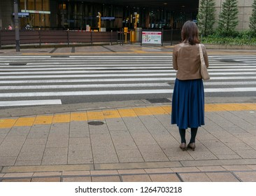 OSAKA, JAPAN-NOV 8, 2018: Back view of unidentified Japanese woman in leather jacket wait for green light to cross a road in Osaka, Japan.
