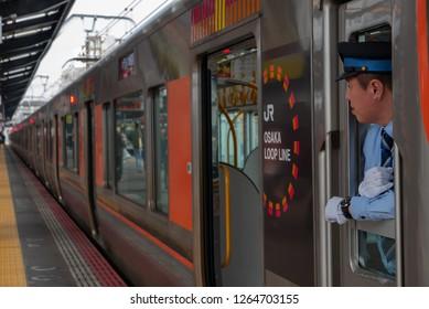 OSAKA, JAPAN-NOVEMBER 12, 2018: Unidentified train driver looks for passengers at Shin-Imamiya station in Osaka, Japan.