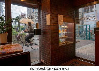 OSAKA, JAPAN-NOVEMBER 9, 2018: Unidentified Japanese woman on a bicycle holding an umbrella cycles in front of a coffee shop in Shin-Imamiya, Osaka, Japan.