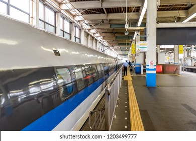 Osaka, JP - JUNE 28, 2017: Gates of Shinkansen high-speed bullet train opening at station for passengers, viewing form railway side, shown as abstract background.