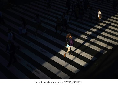 Osaka - Nov. 15, 2018: Artistic light view in evening of pedestrian running at zebra cross in front of Hankyu Umeda station.