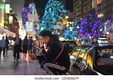Osaka - Nov. 15, 2018: Unidentified Japanese is seen using phone at the street of Dotonbori