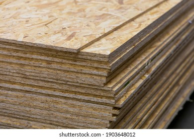 OSB - Oriented Strand Board. Sheet stack in a construction store. Engineered wood product for load-bearing applications in construction - Shutterstock ID 1903648012