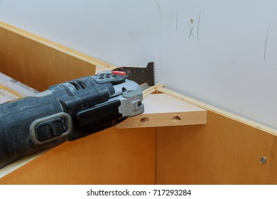oscillating multi-function power tool on kitchen cabinets framing background