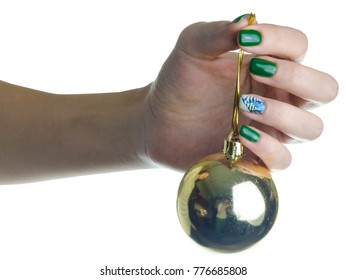 oseup girl hands with New Year's manicure. hanging single golden, gold ball. element of Christmas tree decorations. ball is symbol of winter holiday. art picture on the green nails. round glass sphere