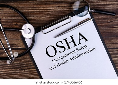 OSHA text written in a notebook lying on a desk and a stethoscope. Medical concept.