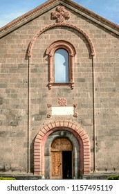 Oshakan,Armenia,19 Februar,2018:Pink openwork arches over the front door, over window and patterned cross on the facade of the Church of St. Mesrop Mashtots in Oshakan
